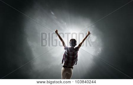 Rear view of woman with hands up facing success
