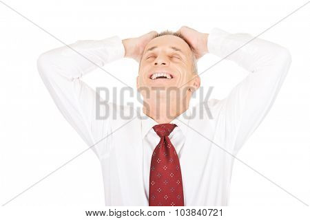 Portrait of businessman holding arms on head.