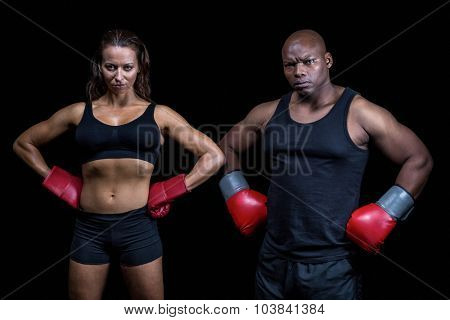 Portrait of male and female boxers with hands on hip against black background