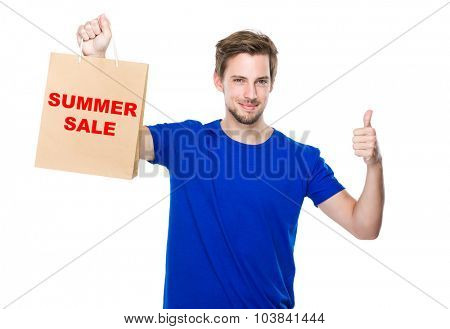 Man with shopping bag and thumb up and showing summer sale