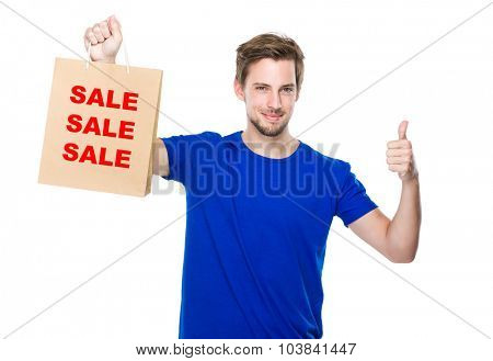 Man with shopping bag and thumb up and showing three words of sale