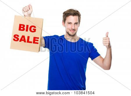 Man with shopping bag and thumb up and showing big sale