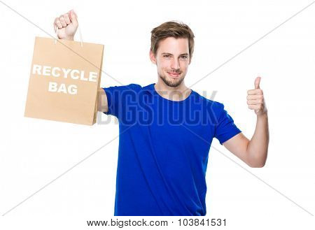 Man with shopping bag and thumb up and showing phrase of recycle bag