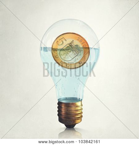 Glass light bulb with euro coin floating inside