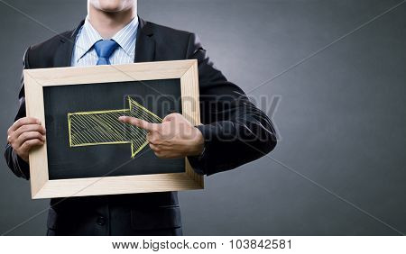 Unrecognizable businessman pointing with finger at arrow on chalkboard