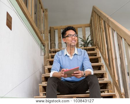 Portrait of young businessman sitting at the stairs in office