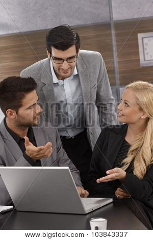 Young businesspeople working together in office, sitting at desk, using laptop computer .