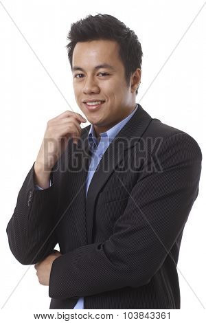 Closeup portrait of young Asian businessman, smiling arms crossed.
