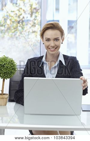 Portrait of happy attractive businesswoman sitting at desk, working with laptop, looking at camera.