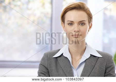 Portrait of attractive young elegant businesswoman looking at camera, serious.