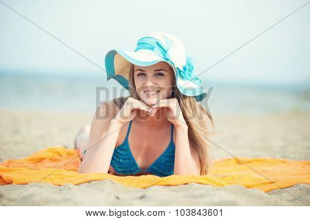 Young lady sunbathing on a beach. Beautiful woman posing