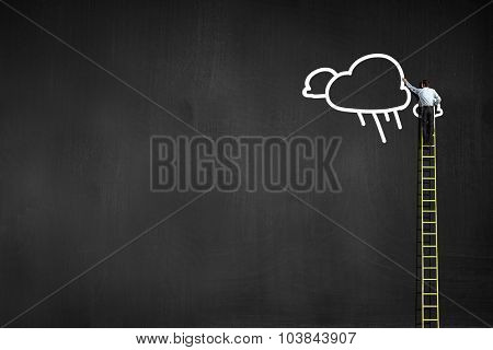 Businessman climbing ladder to top and touching cloud