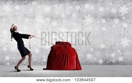 Santa woman pulling huge red gifts bag