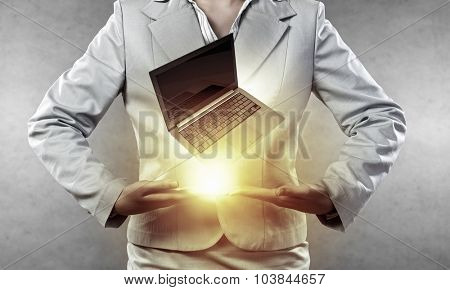 Close up of businesswoman holding laptop in hands