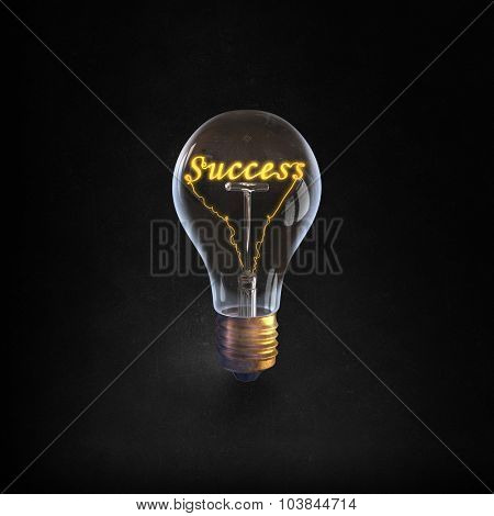 Glowing glass light bulb with success word inside