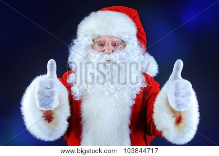 Santa Claus shows thumbs up over black background. Christmas time.
