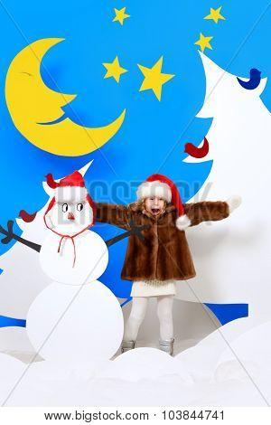 Joyful little girl in a cartoon fairy snowy forest. The magic of Christmas night. Full length portrait.
