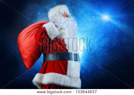 Santa Claus stands with a huge bag of gifts over dark background. Christmas time.