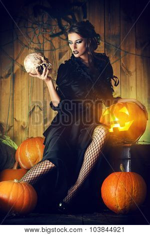 Attractive witch girl in black dress holding a skull in a mysterious abandoned house. Witchcraft, witch. Vampire.  Halloween concept.