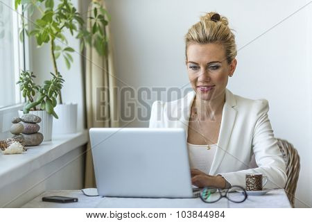 Attractive business woman in the home office working on laptop.