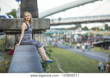 Pretty young lady in the style of 50's sits on the promenade.