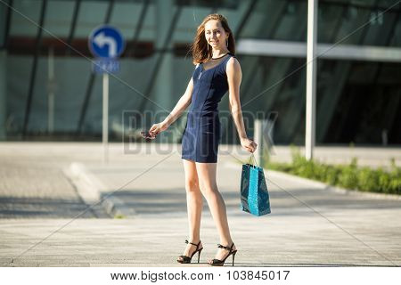 Pretty young shopping-lady in the street with package.