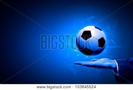 Football manager hold ball on his hand on blue background