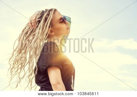 Modern girl with long blonde dreadlocks standing outdoor over blue sky. Boho style fashion.