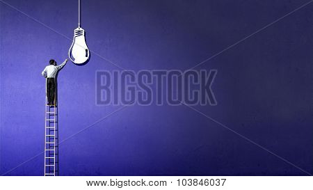 Back view of businessman standing on ladder and reaching light bulb