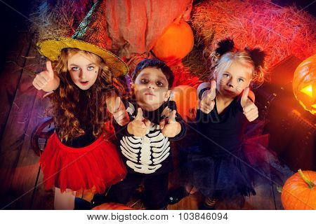 Three children dressed as a witch, a skeleton and a black cat celebrating halloween in a wooden barn with pumpkins. Halloween concept.