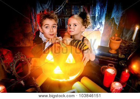 Two cute children dressed as a vampire and a black cat posing with pumpkin in a halloween room. Halloween concept.