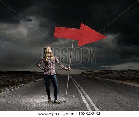 Young girl with arrow signbord in empty room
