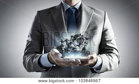 Close up of businessman's hands holding many laptops