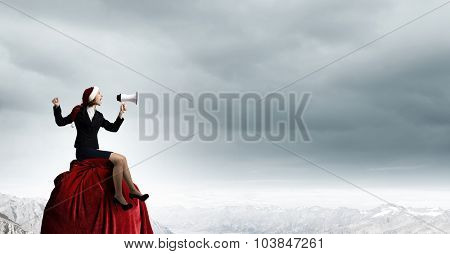 Woman in suit and Santa hat shouting into megaphone