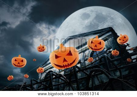 Pumpkins Fly Over Old Fence And Grunge Building At Night Over Cloudy Sky And The Moon