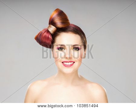 Beautiful smiling girl with a bow haircut and colorful make-up on grey background.