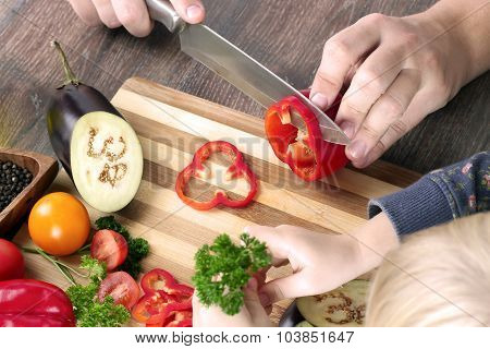 Food, Family, Cooking And People Concept - Man Chopping Paprika On Cutting Board With Knife In Kitch