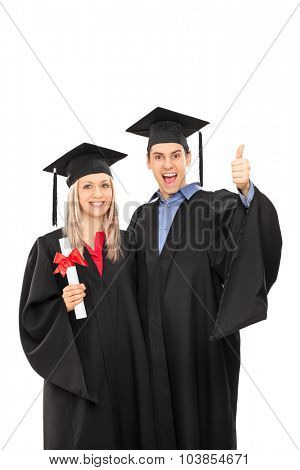 Vertical shot of a delighted man and woman in graduation gowns gesturing happiness isolated on white background