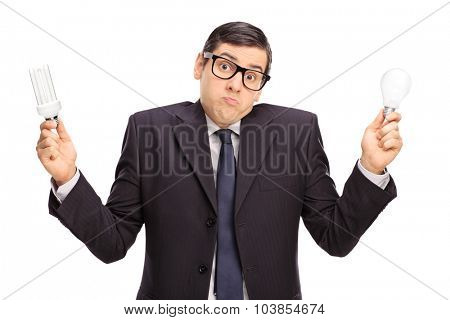 Confused businessman holding a normal light bulb in one hand and an energy saving light bulb in the other isolated on white background