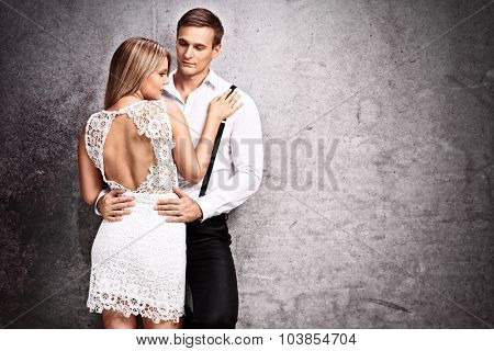 Fashionable young couple posing together by a rusty gray wall