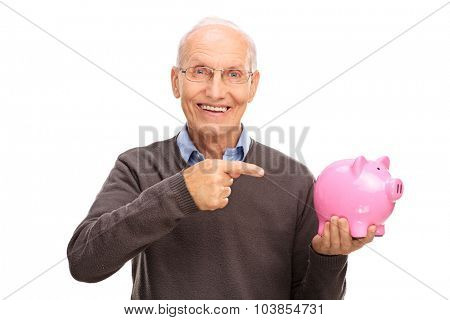 Senior man holding and pointing towards a piggybank and looking at the camera isolated on white background