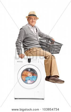 Vertical shot of a senior man waiting for the laundry seated on a washing machine isolated on white background