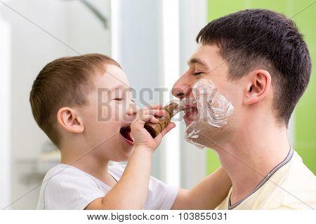 Cute child boy shaving his father in bathroom