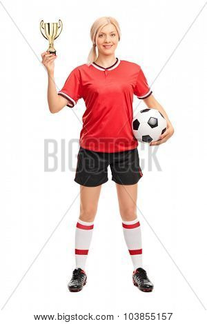 Full length portrait of a young female soccer player holding a ball and a golden trophy isolated on white background