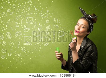 Cute girl blowing hand drawn media icons and symbols on green background