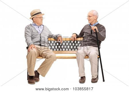 Studio shot of a two senior men arguing with each other seated on a wooden bench isolated on white background