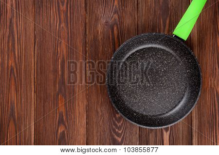 Frying pan on wooden table. Top view with copy space