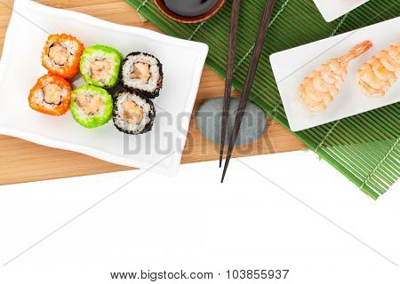 Sushi maki and shrimp sushi on bamboo board. Isolated on white background with copy space