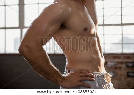 Midsection of a muscular man posing at the gym