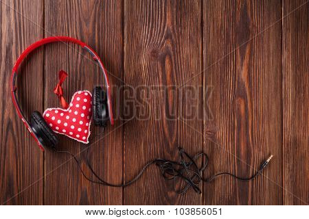 Red heart with headphones on wooden table with copy space. Valentine's day concept.